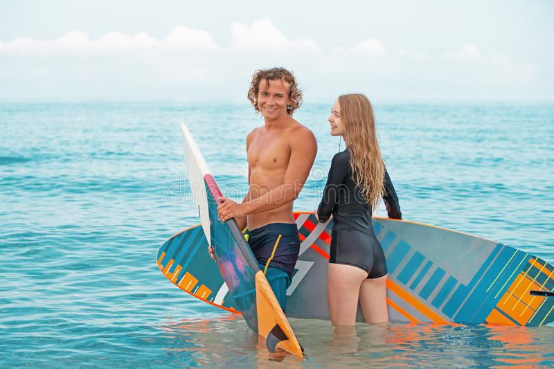 Surfers at the beach- Smiling couple of surfers walking on the beach and having fun in summer. Extreme sport and stock photo