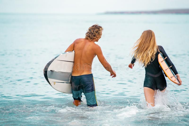 Surfers at the beach- Smiling couple of surfers walking on the beach and having fun in summer. Extreme sport and. Surfers at the beach- Smiling couple of surfers stock photos
