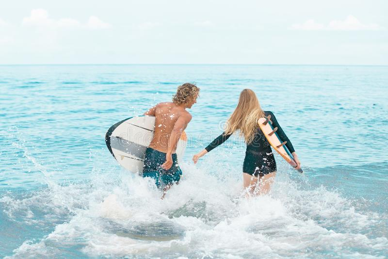 Surfers at the beach- Smiling couple of surfers walking on the beach and having fun in summer. Extreme sport and. Surfers at the beach- Smiling couple of surfers stock photo