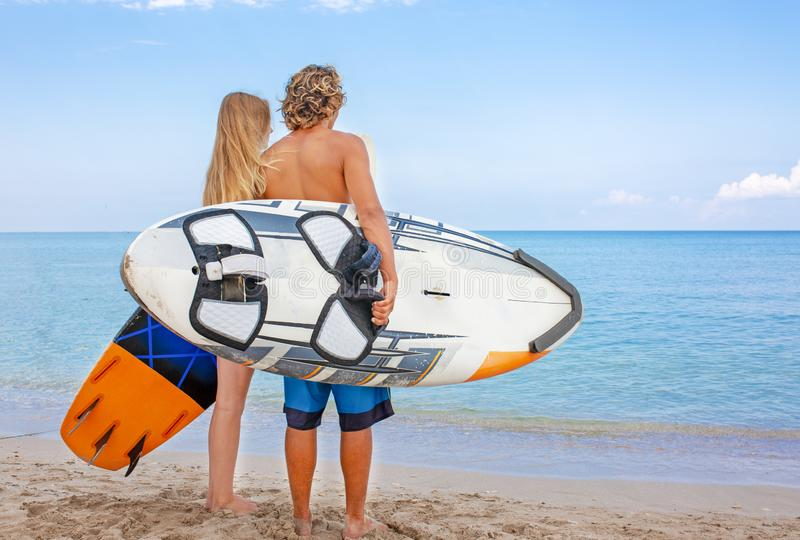 Surfers at the beach- Smiling couple of surfers walking on the beach and having fun in summer. Extreme sport and stock photography