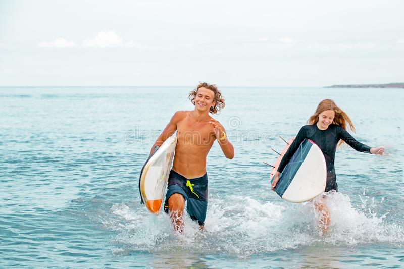 Surfers at the beach- Smiling couple of surfers walking on the beach and having fun in summer. Extreme sport and. Surfers at the beach- Smiling couple of surfers stock photography