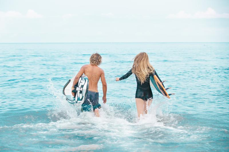 Surfers at the beach- Smiling couple of surfers swiming and having fun in summer. Extreme sport and vacation concept royalty free stock photography
