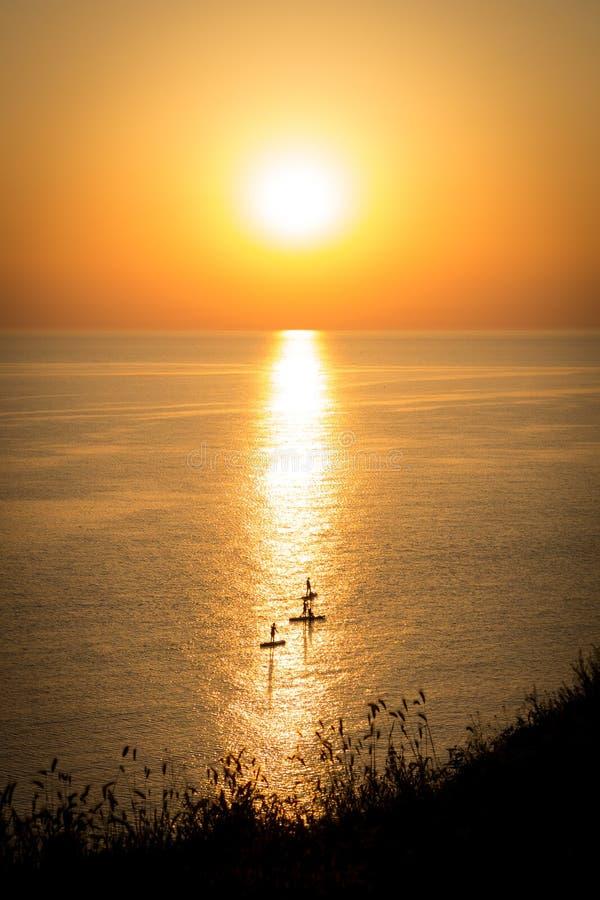 Surfers bij Zonsondergang stock afbeeldingen