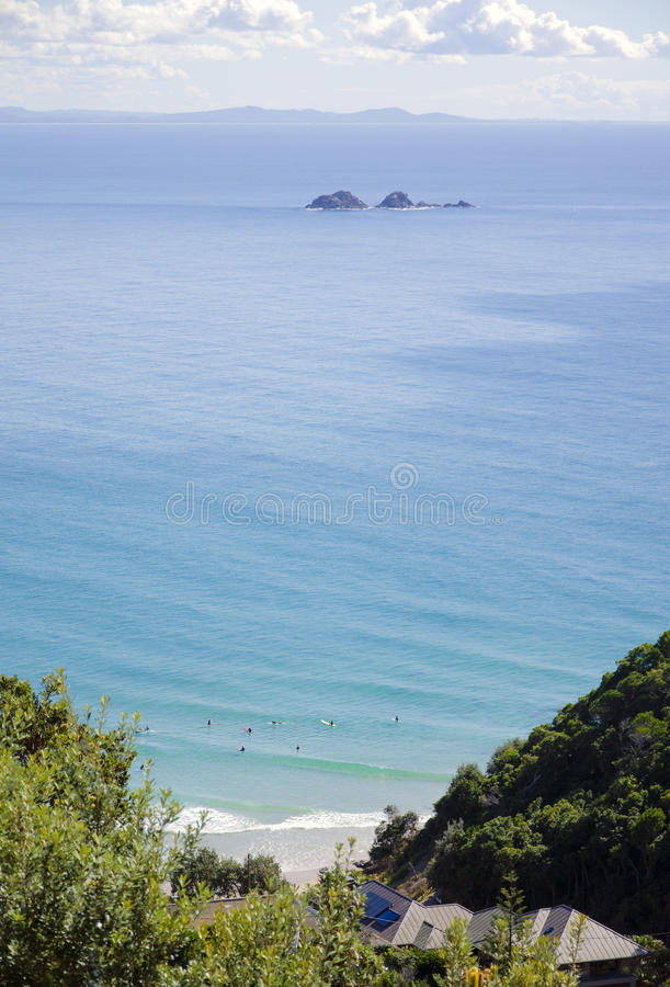 Surfers at Byron Bay Australia overlooking Julian Rocks. Longboarder surfers waiting for a wave at Tallow Beach, Byron Bay in New South Wales, Australia. Julian royalty free stock image