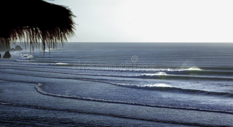 Surfers die het surfen golven berijden op de kustlijn van Bali stock foto's
