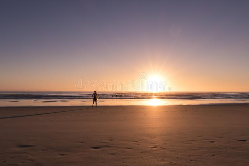 Surfers die naar het strand tijdens zonsopgang lopen stock foto's