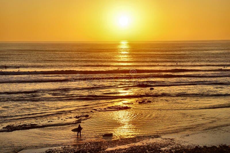 Surfers entrant au coucher du soleil photo stock