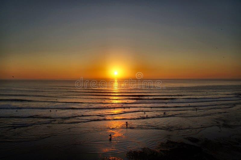 Surfers entrant au coucher du soleil photo libre de droits