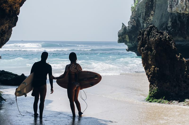 Surfers getting into the sea, ready to surf the waves. Kuta beach, Bali royalty free stock images