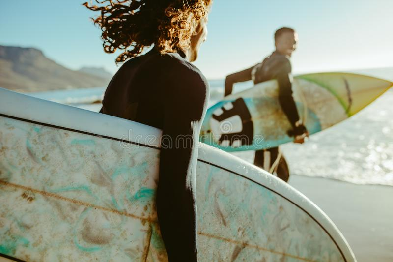 Surfers going for surfing in the sea. Two young men with surfboard going for surfing in the sea. Surfers carrying surfboards running on the beach stock image