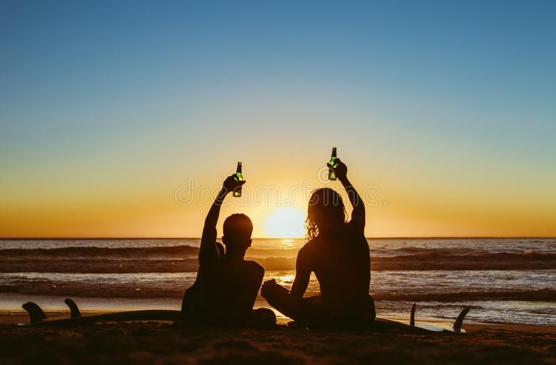 Surfers having a party at beach. Rear view of two young surfers toasting beers on the beach and looking at the sunset. Young men partying during sunset at the royalty free stock photo