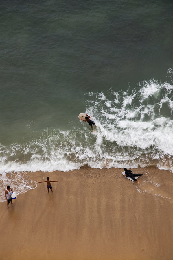 Surfers in Hawaii. Surfers and swimmers in Kahana beach, Maui, Hawaii royalty free stock image