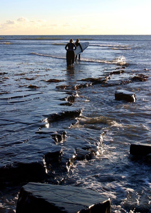 Surfers at Kimmeridge Bay, Dorset royalty free stock photos
