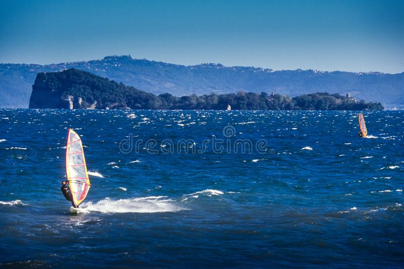 Bolsena, Lazio - Italy. Surfers on the lake of Bolsena Italy - The medieval town with castle on Lake Bolsena, region Latium, central Italy royalty free stock image