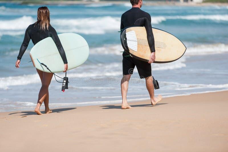Surfers marchant le long de la plage avec des planches de surf photos stock