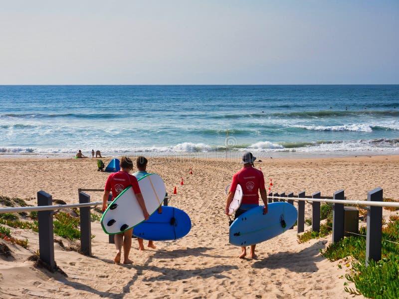 Surfers marchant sur la plage sablonneuse, Sydney, Australie photos libres de droits