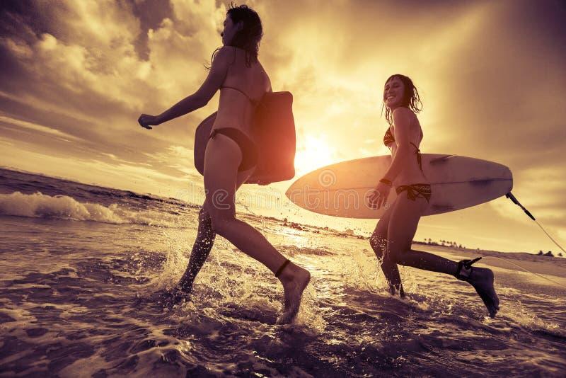 Surfers met raad stock afbeelding