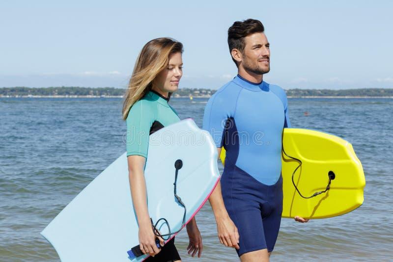 Surfers op strand die pret in de zomer hebben royalty-vrije stock afbeeldingen