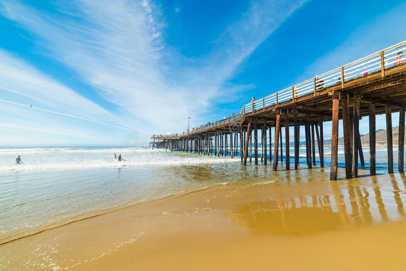 Surfers by Pismo Beach pier. California royalty free stock images
