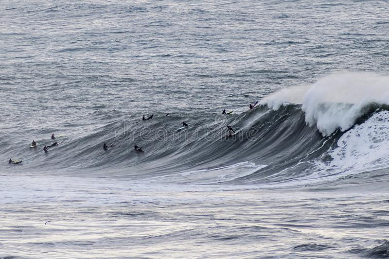 Surfers riding huge waves on the west coast, close to Pillar Point and Mavericks Beach, Half Moon Bay, California royalty free stock photos
