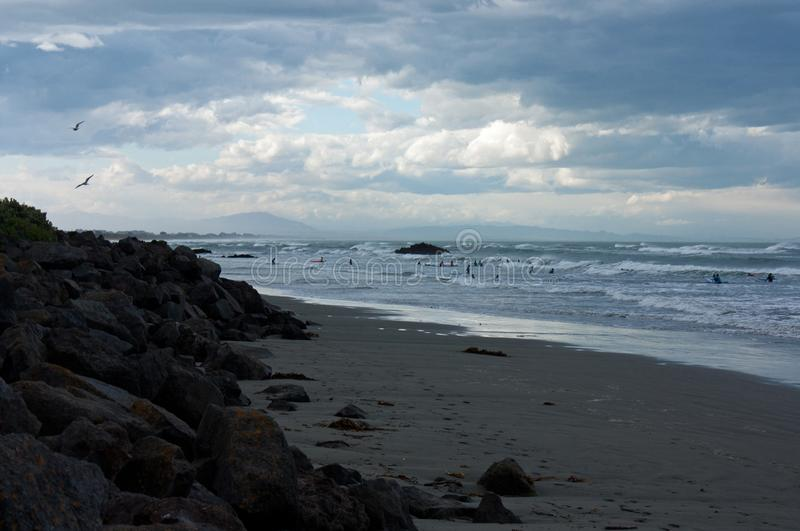 Surfers in the sea at Sumner Beach in Christchurch in New Zealand. Surfers in a wavy sea at Sumner Beach in Christchurch in New Zealand stock image