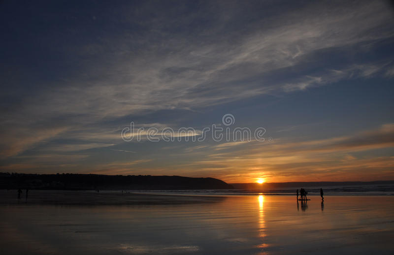 Surfers at sunset royalty free stock image