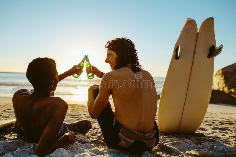 Surfers toasting beers on the beach royalty free stock photo