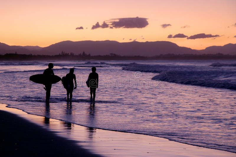 Surfers walking on the beach during the sunset royalty free stock photos