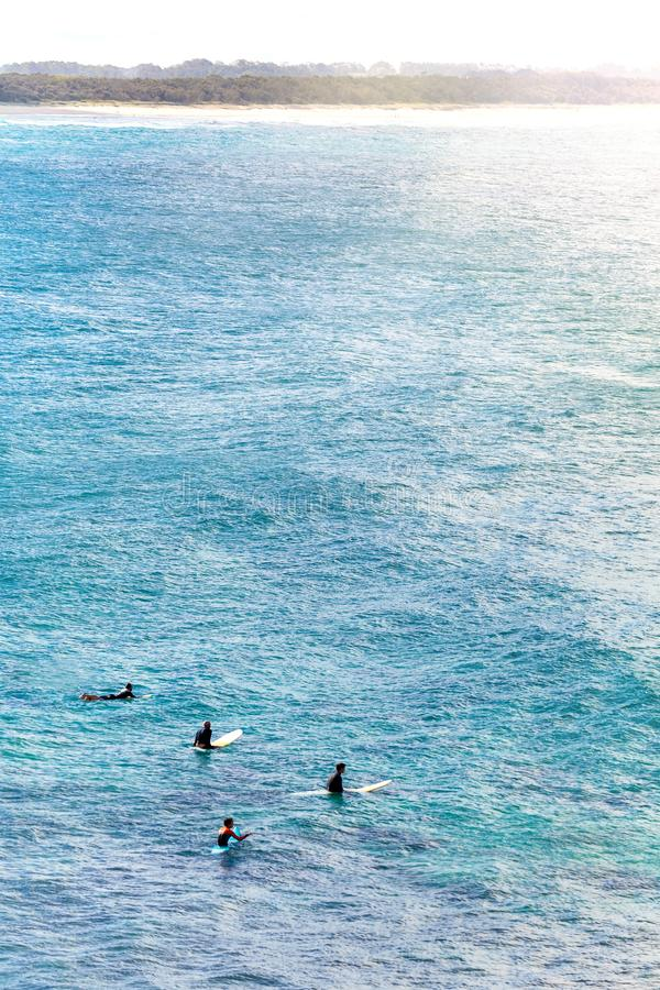 Surfers in the Water at Cabarita Beach in Australia. A group of surfers wait patiently in the water for larger waves at Cabarita Beach in New South Wales stock photo