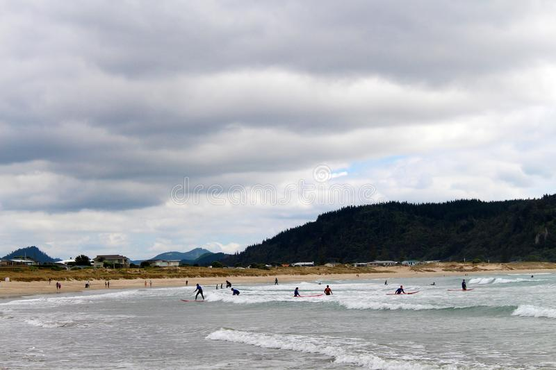 Surfers on Whangamata beach in New Zealand stock images