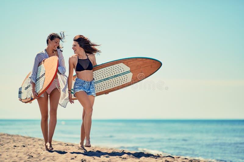 Surfersmeisjes op strand die pret in de zomervakantie hebben Extreem SP stock afbeeldingen