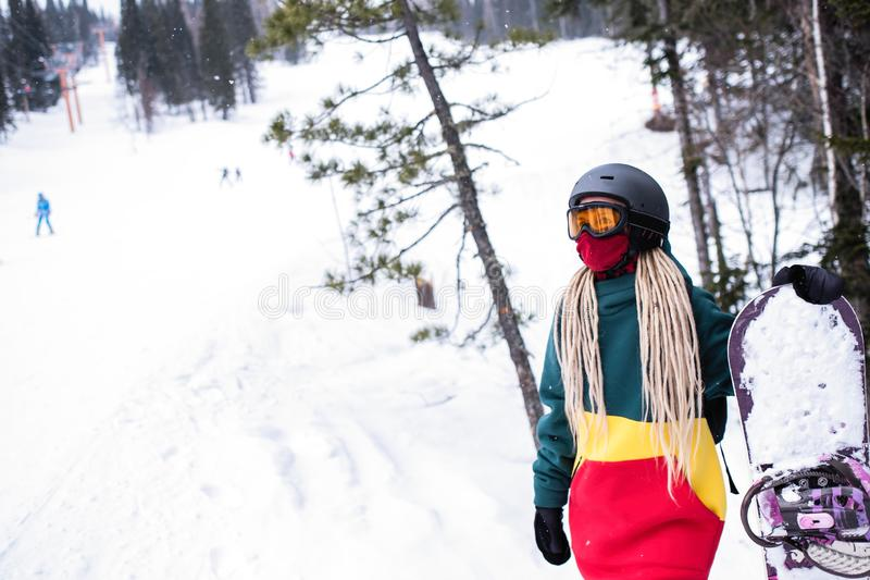 Surfeur de jeune femme qu'il se tient avec un surf des neiges près des pentes de ski photo stock
