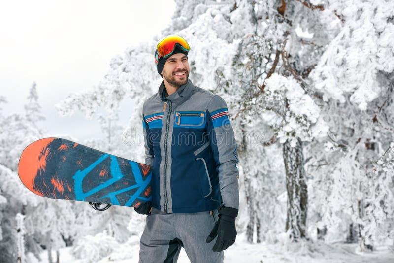 Surfeur de sourire tenant le conseil pour faire du surf des neiges photographie stock