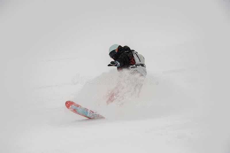 Surfeur professionnel montant en bas de la pente de montagne pure dedans photo stock