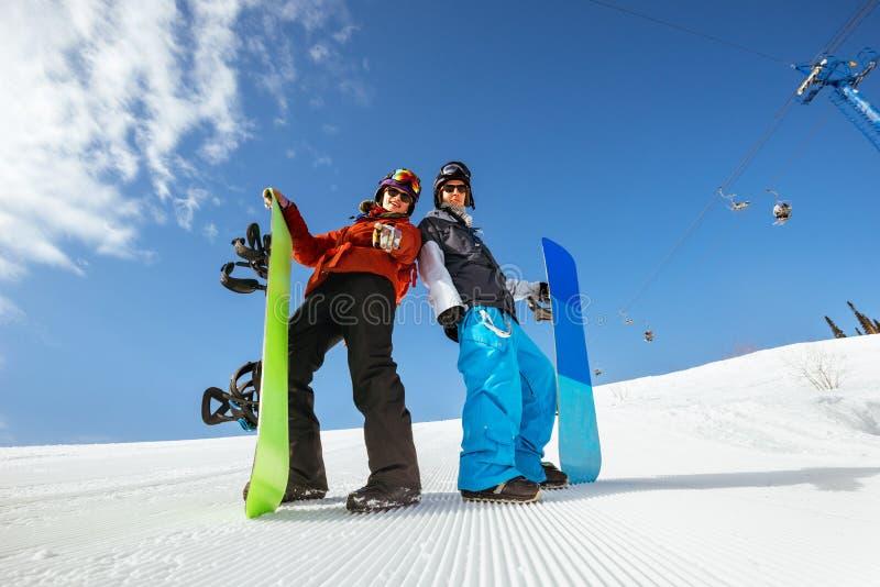 Surfeurs d'amis de groupe faisant du surf des neiges la montagne de pente photos stock