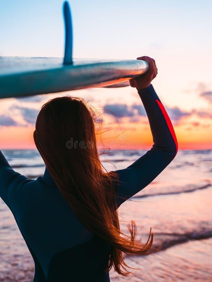 Surfez la fille avec de longs cheveux tenant la planche de surf sur la plage au coucher du soleil ou au lever de soleil Surfer et photo libre de droits