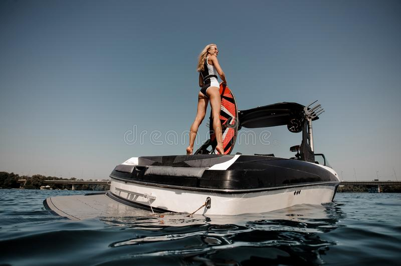 Surfgirl in sunglasses standing on a boat royalty free stock images
