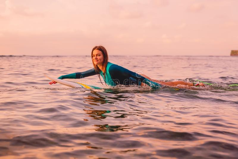 Surfgirl with perfect body on a surfboard floating in ocean. Surfing at sunset royalty free stock photography
