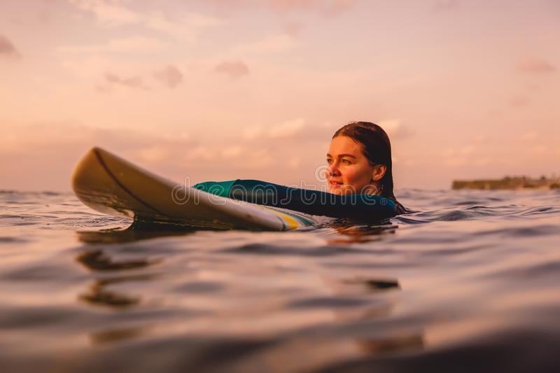 Surfgirl with perfect body on a surfboard floating in ocean. Surfing at sunset royalty free stock photos