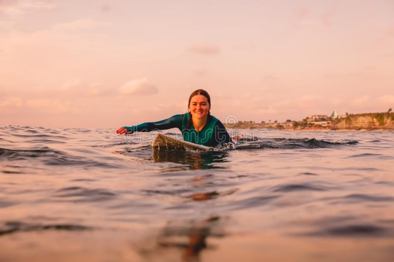 Surfgirl with perfect body on a surfboard floating in ocean. Surfing at sunset stock photography