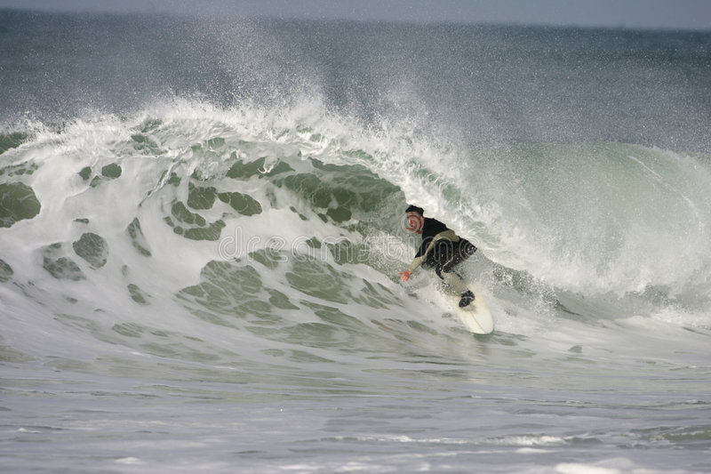 Surfing. Young man with his surfboard executing a big move on a wave stock photo