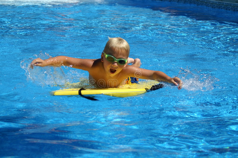 Surfing. A boy with surfing desk in the pool royalty free stock photography