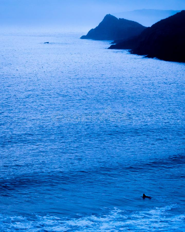 Surfing alone in the immensity of the ocean in France stock photos