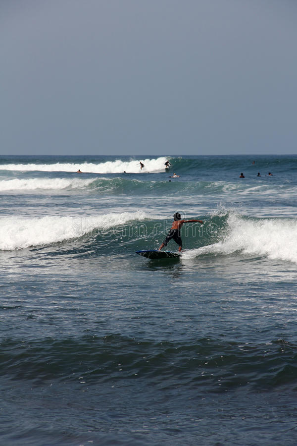 Surfing in Bali. Boy do surfing on waves. Some surfers are nearby. stock photos