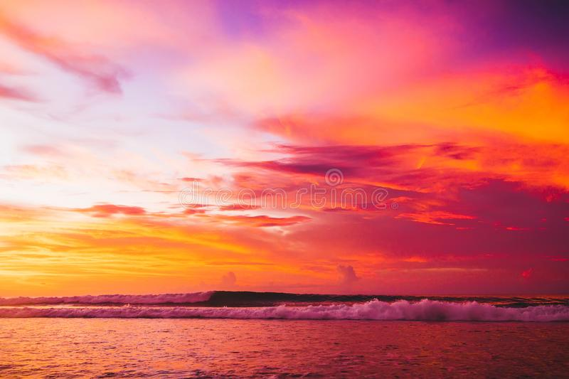 Surfing colored ocean wave falling down at sunset or sunrise time royalty free stock image