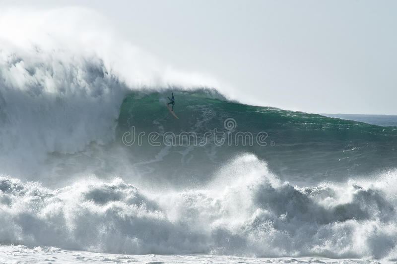 Surfing Dangerous Big Waves. This is a professional big wave surfer trying to manoeuvre himself down a mountain of water. His surfboard is 2,5 meters long, the stock photos