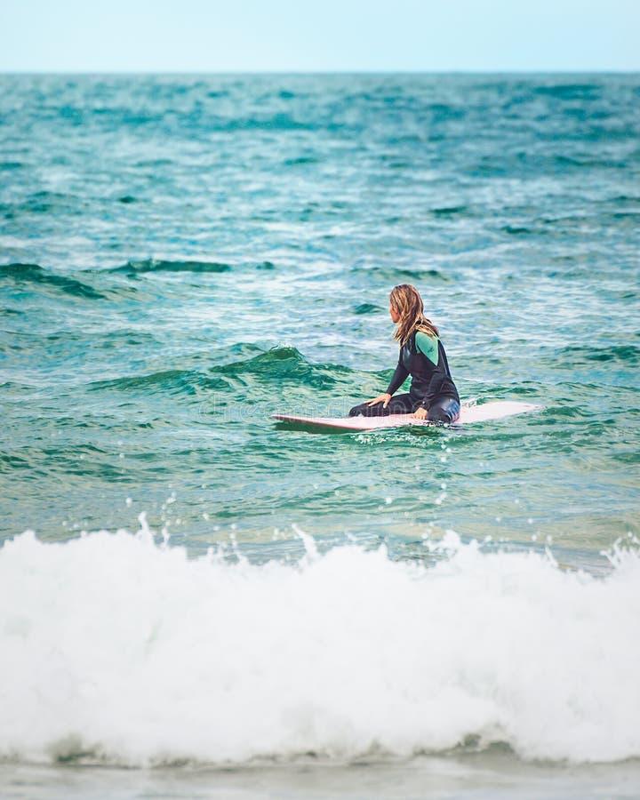 Surfing dziewczyny czekania na wyprostowywają fala w oceanie obraz stock