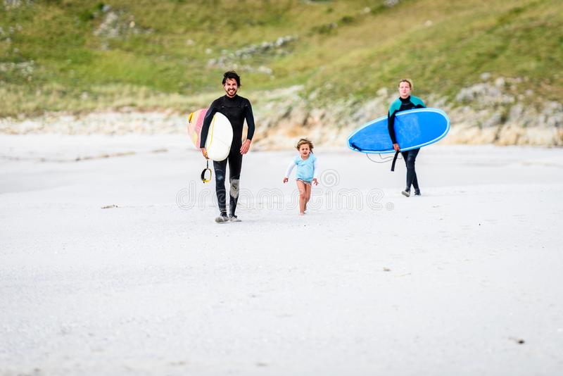 Surfing family with surfboard is walking on the sandy beach. Daughter is greeting parents after surfing session in atlantic ocean in Galicia, Spain. Mother royalty free stock photography