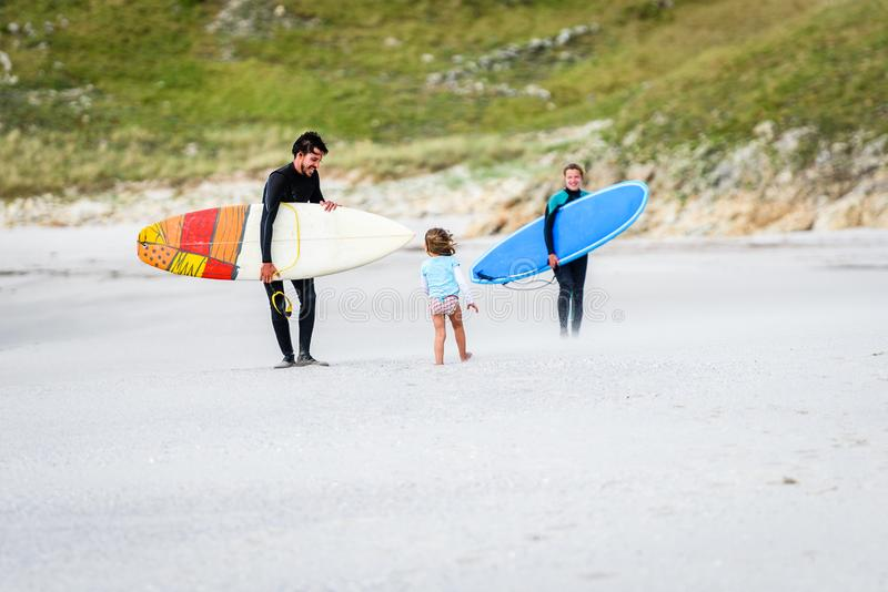 Surfing family with surfboard is walking on the sandy beach. Daughter is greeting parents after surfing session in atlantic ocean in Galicia, Spain. Mother stock image