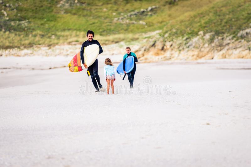 Surfing family with surfboard is walking on the sandy beach. Daughter is greeting parents after surfing session in atlantic ocean in Galicia, Spain. Mother stock photos